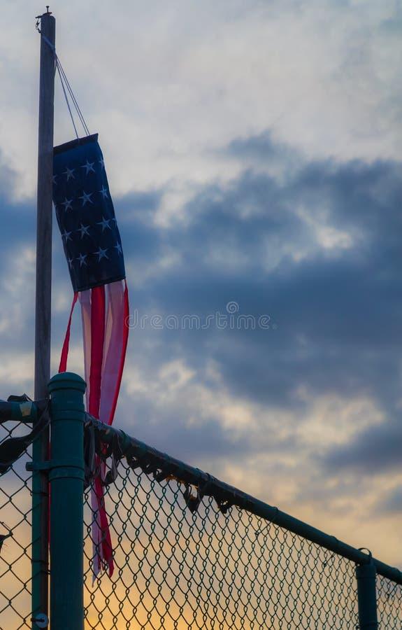 Eine amerikanische Flagge auf einem Flaggen-Posten während des Sonnenuntergangs lizenzfreie stockfotos