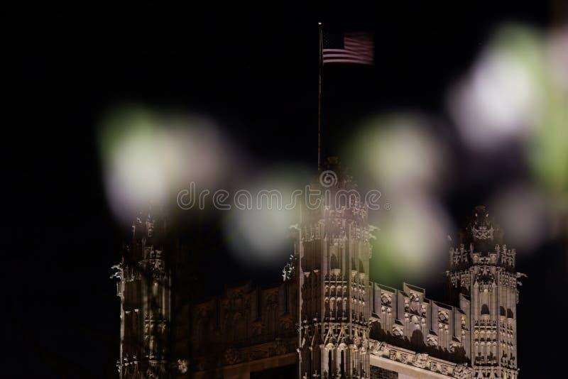 Eine amerikanische Flagge bewegt hoch über einen Turm mit gotischer Architektur, mit unscharfen Vordergrundelementen wellenartig stockbild