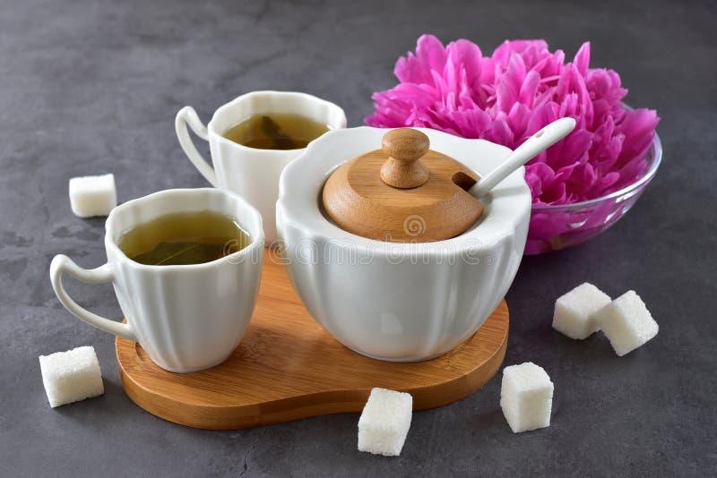 Eine angenehme Teezusammensetzung von zwei Schalen, von Zuckerschüssel und von Pfingstrosenblume lizenzfreies stockfoto