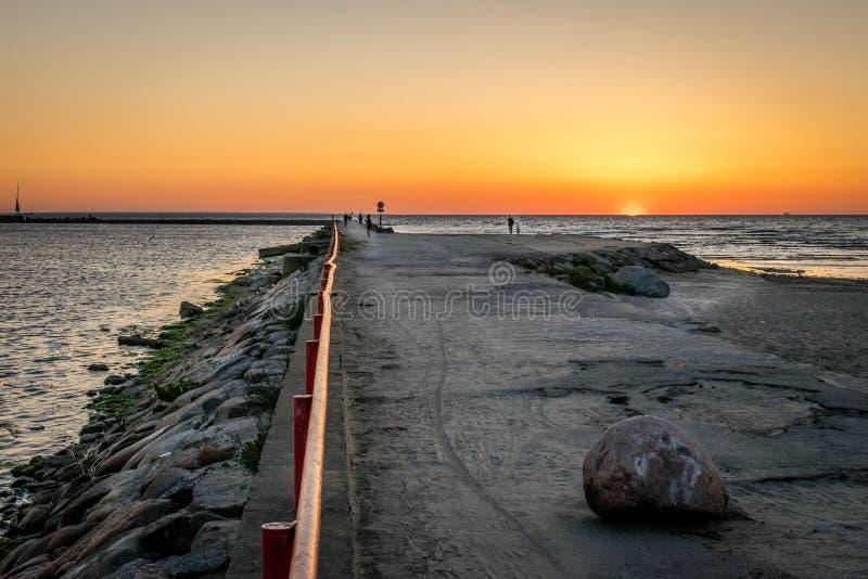 Eine Anlegestelle oder ein Pier mit silhouettierten Leuten mit einem Sonnenuntergang in Meer stockfotos