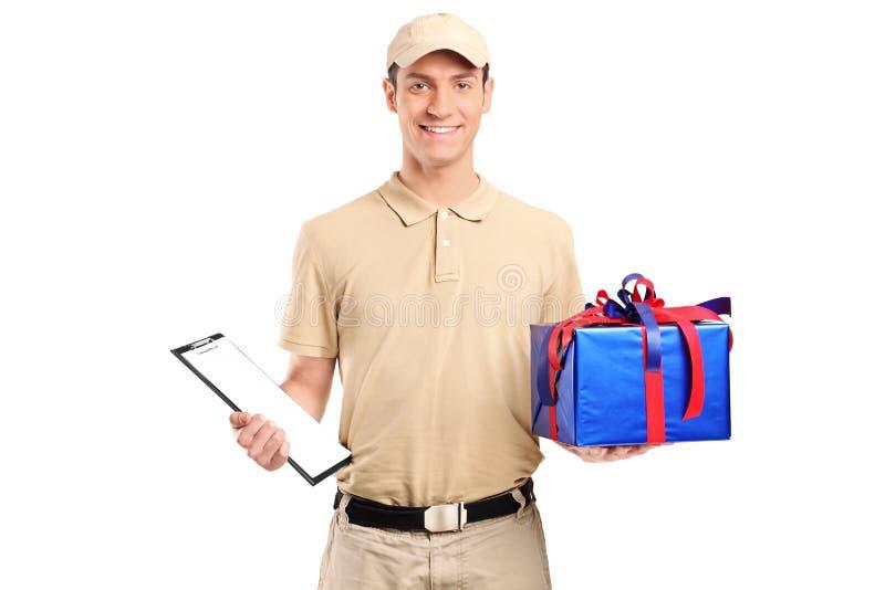 Eine Anlieferungsperson, die einen großen Geschenkkasten liefert lizenzfreies stockfoto