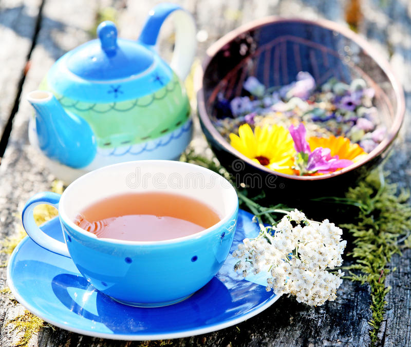 Eine Anordnung für einen blauen Teetopf und eine Tasse Tee mit Blumendekoration stockfotos