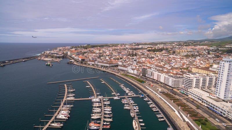 Eine Ansicht über Ponta Delgada vom Jachthafen, Sao Miguel, Azoren, Portugal Festgemachte Yachten und Boote entlang den Hafenpier lizenzfreies stockfoto