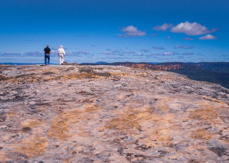 Eine Ansicht der blauen Berge in Syndey, Birne Australiens AP, wie zwei Männer dem Rand eines flachen aber strukturierten und far lizenzfreie stockbilder