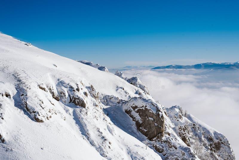 Eine Ansicht von der Spitze des Berges zu den Klippen bedeckt mit Schnee an einem sonnigen Tag lizenzfreies stockfoto