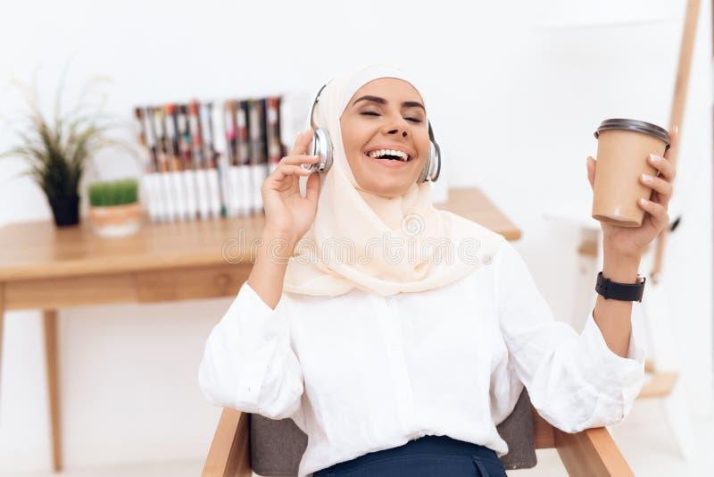 Eine arabische Frau im hijab hört Musik auf Kopfhörern lizenzfreies stockbild