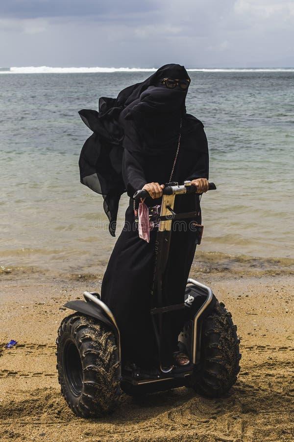 Eine arabische Frau reitet ein segway auf einen Strand stockfotos