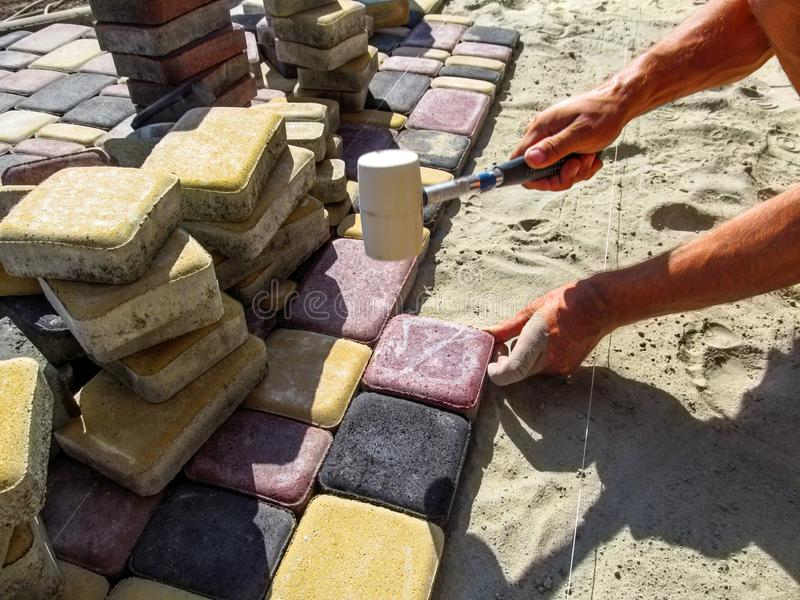 Eine Arbeitskraft bei dem Legen von mehrfarbigen Pflastersteinen stockbild