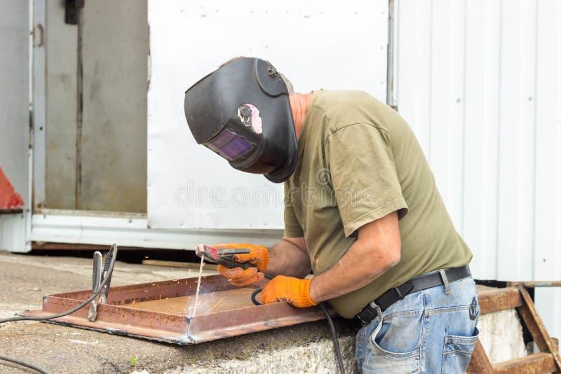 Eine Arbeitskraft in einer schweißenden Maske führt Schweißarbeit auf dem Metall durch Bondteile Metall unter hoher Temperatur stockfotografie
