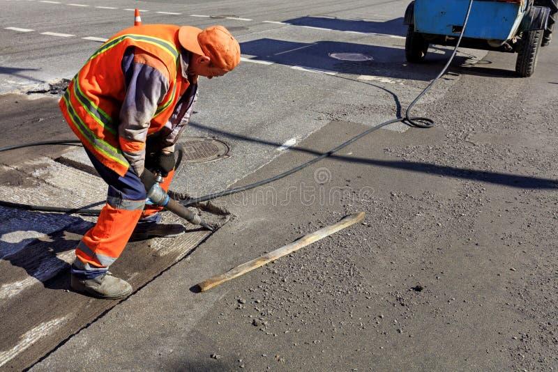 Eine Arbeitskraft klärt einen Teil vom Asphalt mit einem pneumatischen Jackhammer während des Straßenbaus stockfotografie