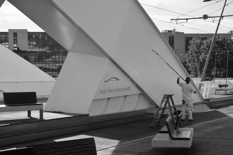 Eine Arbeitskraft streicht eine Brücke neu stockbild
