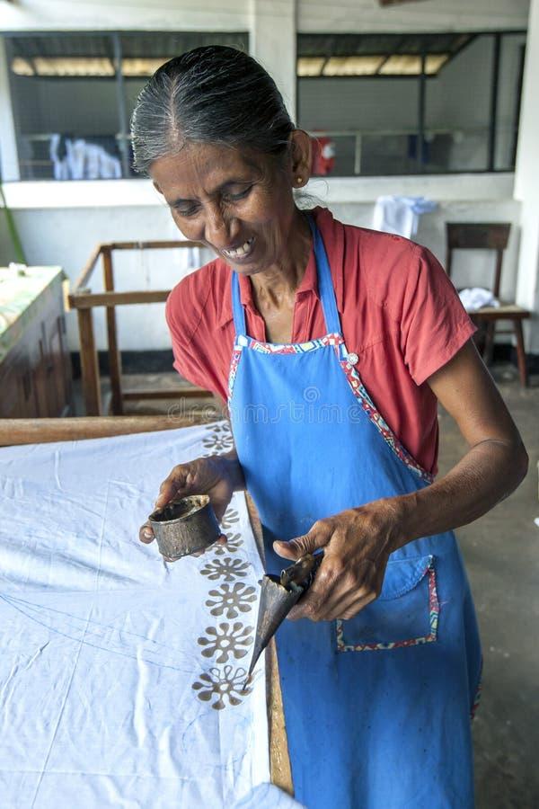 Eine Arbeitskraft trägt Wachs an einem Batik an der Baba Batik-Fabrik in Matale in Sri Lanka auf lizenzfreie stockfotografie