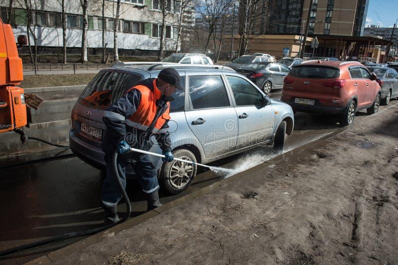 Eine Arbeitskraft wäscht die Straße in den Plätzen, in denen Autos geparkt werden stockfotografie
