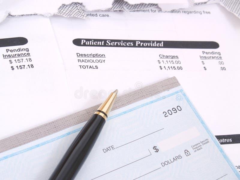 Eine Arztrechnung und ein Scheckbuch stockbild