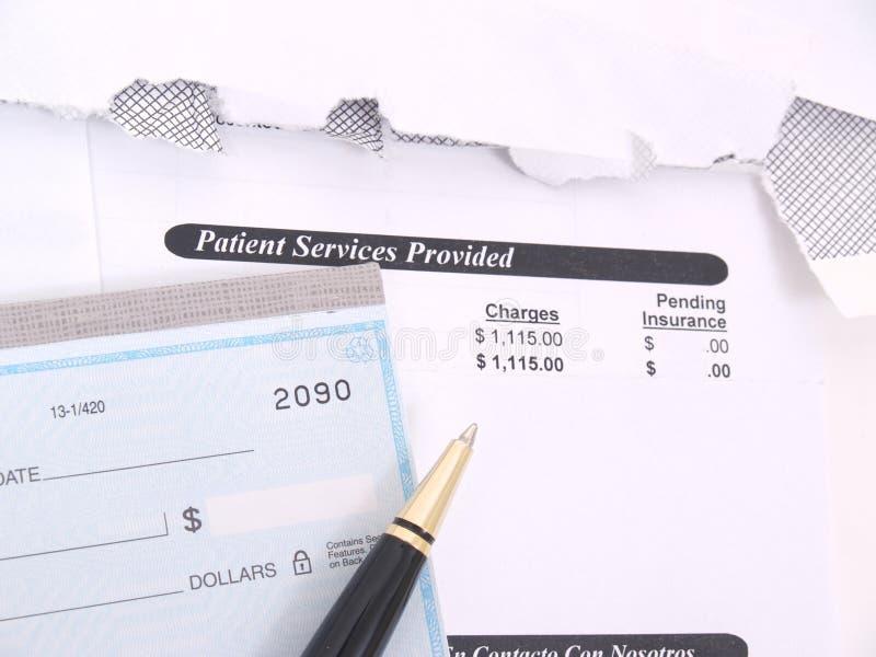 Eine Arztrechnung und ein Scheckbuch stockbilder