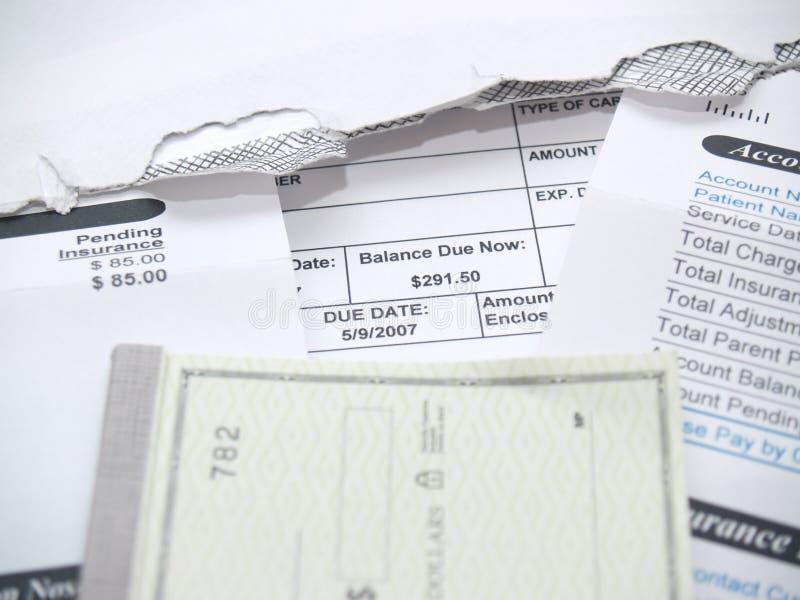Eine Arztrechnung und ein Scheckbuch lizenzfreie stockfotografie
