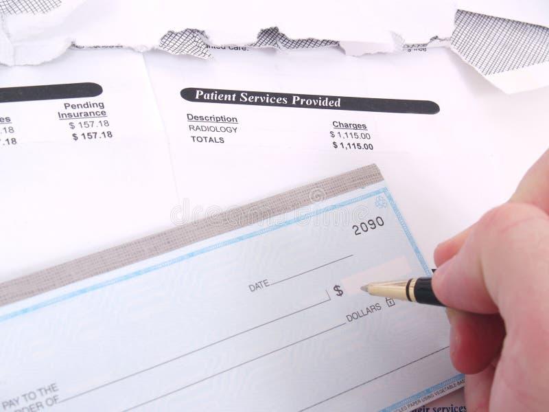 Eine Arztrechnung und ein Scheckbuch lizenzfreie stockbilder