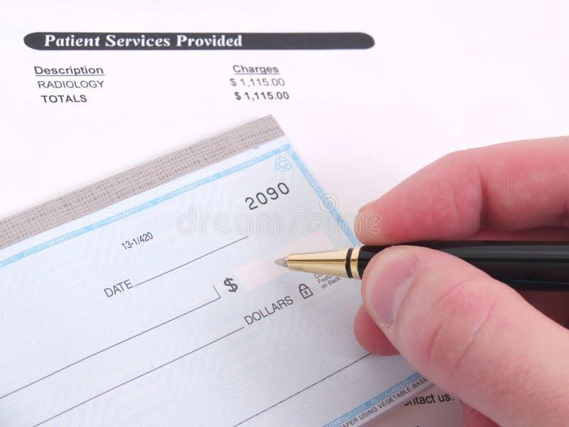 Eine Arztrechnung und ein Scheckbuch stockfotografie