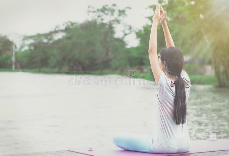 Eine Asiatin meditiert und Yoga in der Ufergegend auf einem hölzernen stockfoto