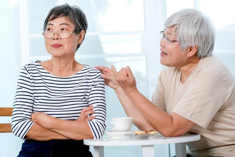 Eine asiatische ältere Frau versuchen, bis die andere während der Teezeit nahe Balkon im Haus zu versöhnen lizenzfreie stockfotos