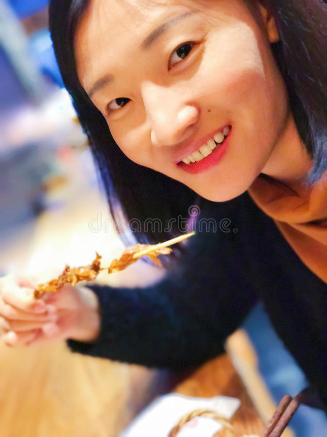 Eine asiatische Frau, die an der Kamera lächelt stockfotos
