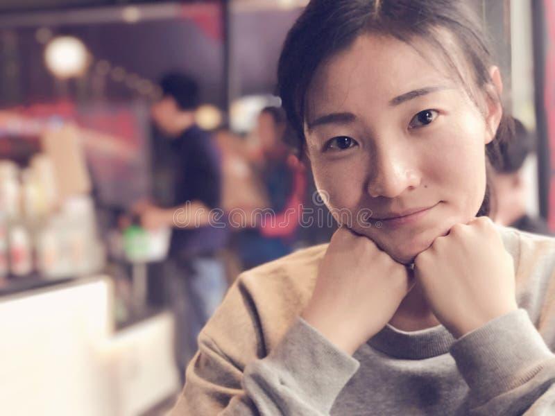 Eine asiatische Frau, die an der Kamera lächelt lizenzfreie stockbilder