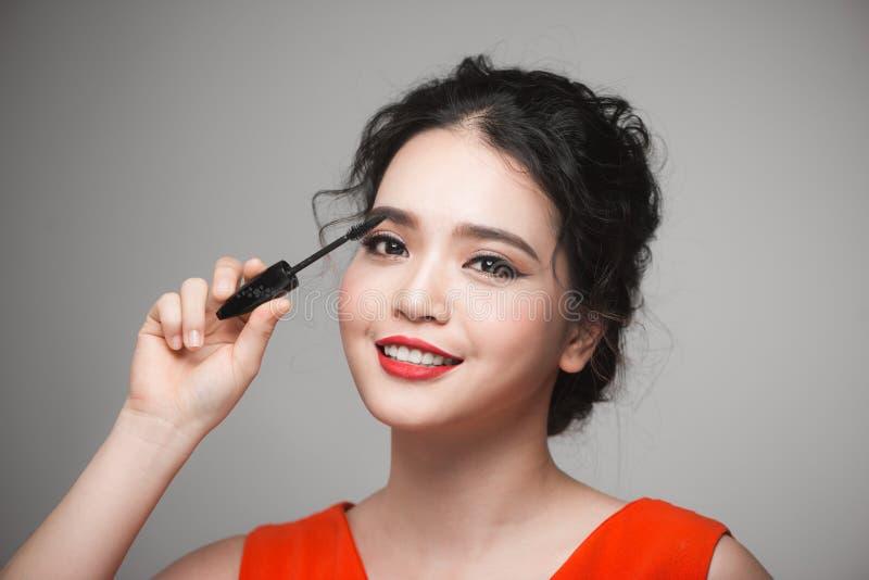 Eine asiatische Frau, die Wimperntusche auf ihren Wimpern anwendet stockbild