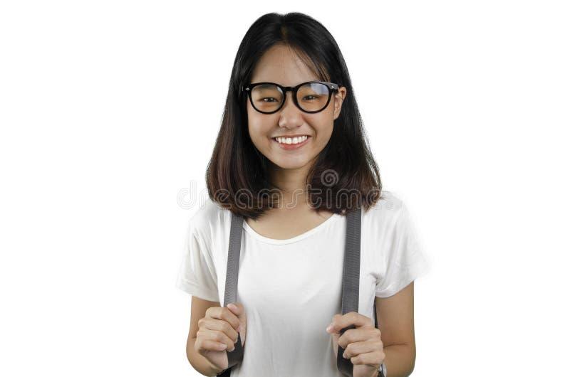 20 eine asiatische junge hübsche Frau, die einen Rucksack mit weißem Hintergrund lächelt und trägt lizenzfreies stockbild