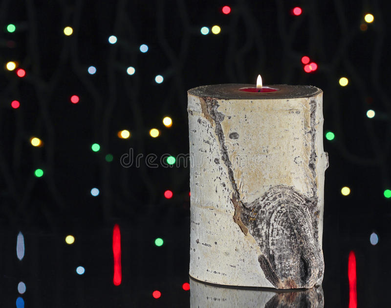 Eine aspen-Protokoll-Kerze und Weihnachtsleuchten stockfoto