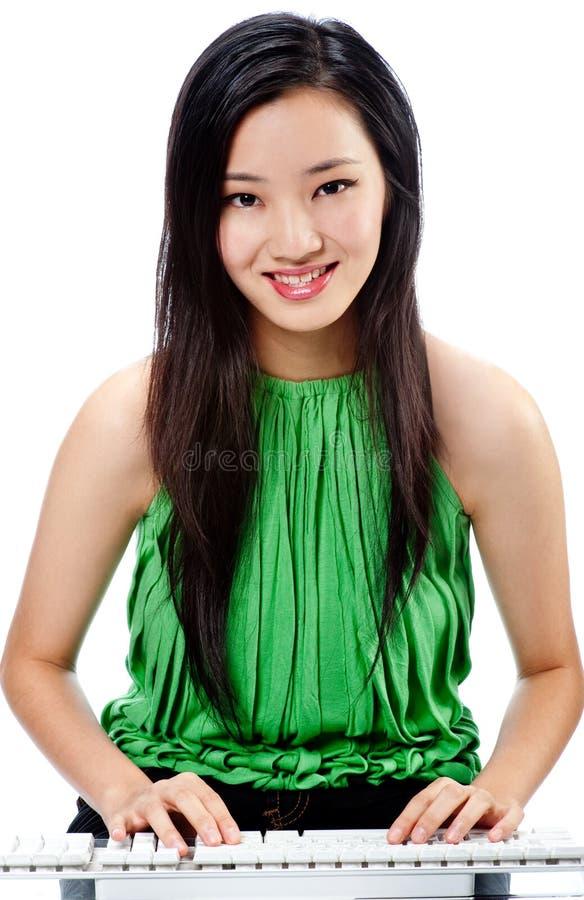 Eine attraktive asiatische Frau mit Tastatur lizenzfreies stockfoto