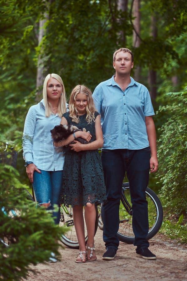Eine attraktive Familie kleidete in der zufälligen Kleidung auf einer Fahrradfahrt mit ihrem netten kleinen Spitzhund an und stan lizenzfreies stockfoto