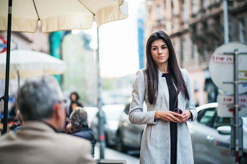 Eine attraktive Geschäftsfrau, die draußen auf einem Bürgersteig in einer Stadt steht stockbild