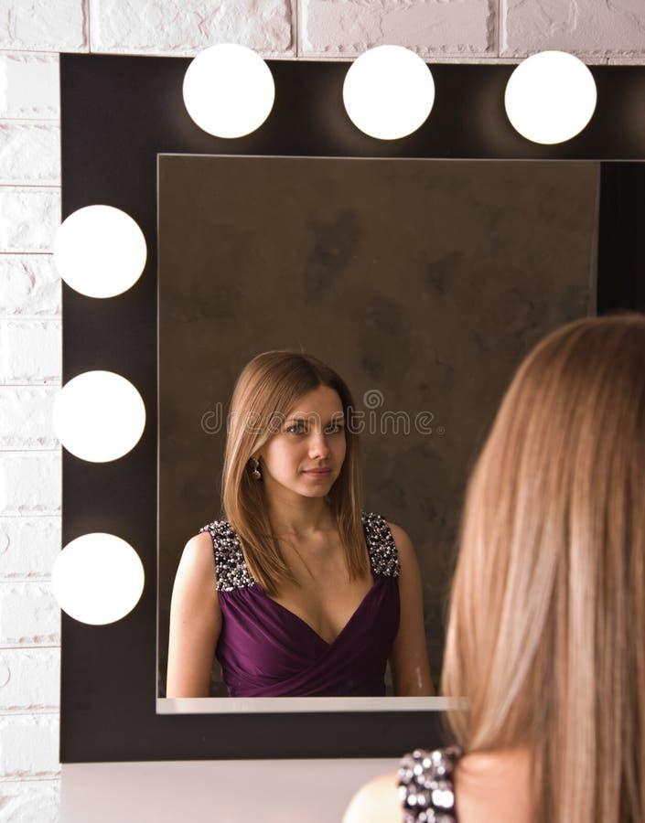 Eine attraktive junge Frau, die im Spiegel schaut stockfoto