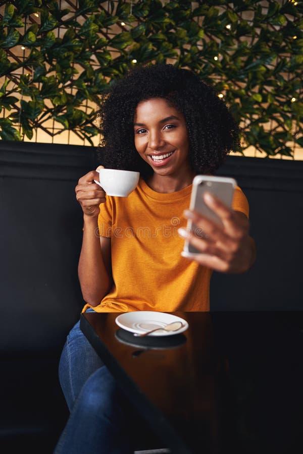 Eine attraktive lächelnde junge Frau, die selfie am Handy im Café nimmt stockbild