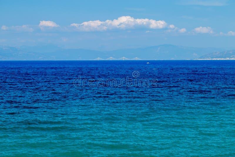 Eine ausgezeichnete Ansicht über den schönen blaugrünen Meeresspiegel zu entfernten Rio Antirio Bridge lizenzfreies stockfoto