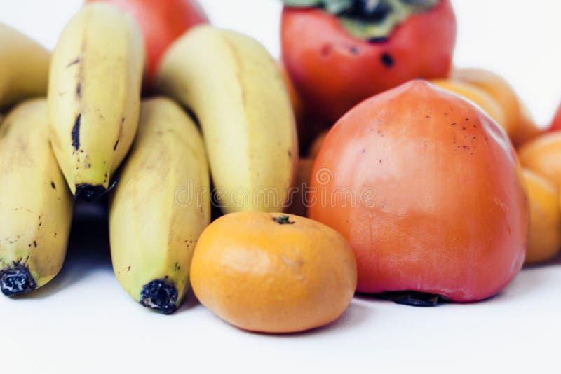 Eine Auswahl von vereinbarten verschiedenen frischen Früchten von Bananen, von Mandarinen, von Persimonen und von Zitronen auf we lizenzfreies stockfoto