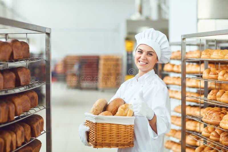 Eine Bäckerfrau, die einen Korb von gebacken in ihren Händen an der Bäckerei hält lizenzfreies stockbild