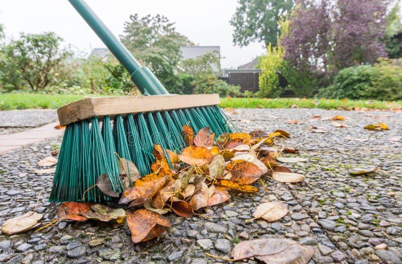 Eine Bürste und ein Stapel von Blättern im Garten lizenzfreie stockbilder