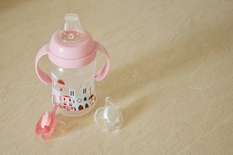 Eine Babyflasche für Getränke und zwei Nippel auf einem Leuchtpult lizenzfreie stockfotografie