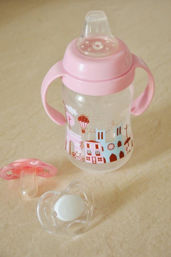 Eine Babyflasche für Getränke und zwei Nippel auf einem Leuchtpult lizenzfreie stockbilder