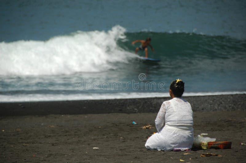 Eine Balinesedame und ein Surfer tun Morgenritual stockfotografie