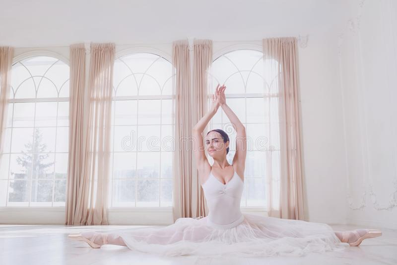 Eine Ballerina auf einer Schnur in der weißen Kleidung in einem weißen Studio stockbilder