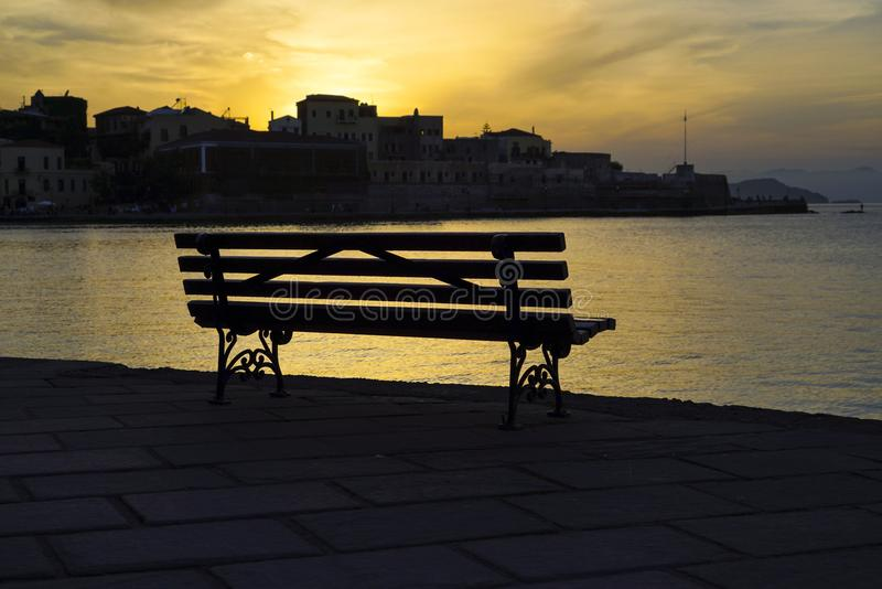 Eine Bank durch Meer bei Sonnenuntergang stockfotografie