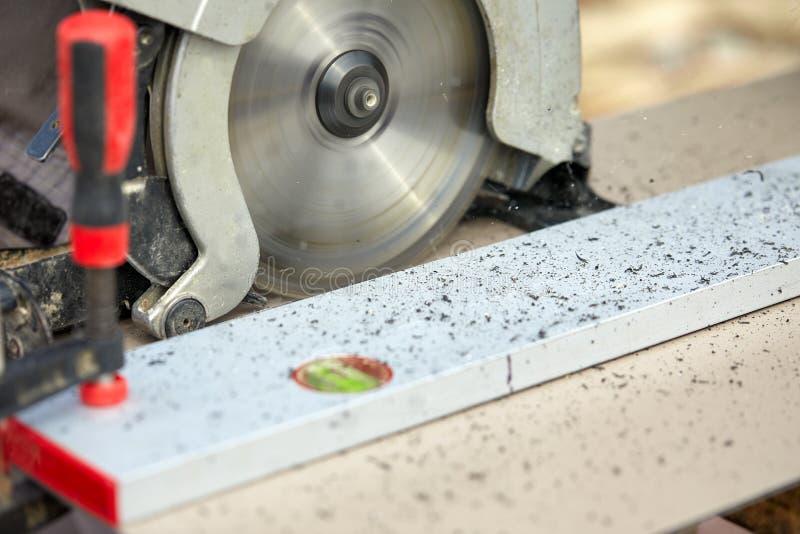 Eine Bauunternehmerarbeitskraft, die eine Wurm-gesteuerte Handkreissäge verwendet, um Bretter und Plastik zu schneiden aufbau lizenzfreies stockbild