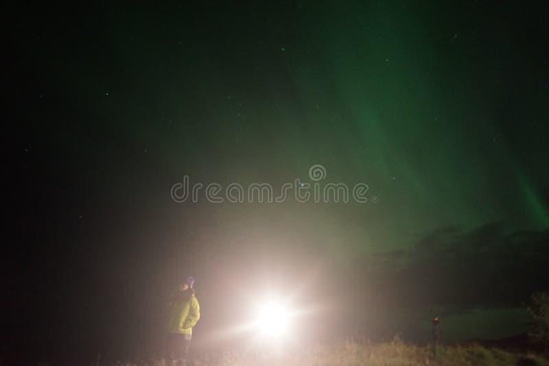 Eine beleuchtete Lampe durch Wanderer auf einem Gebiet nachts lizenzfreies stockfoto