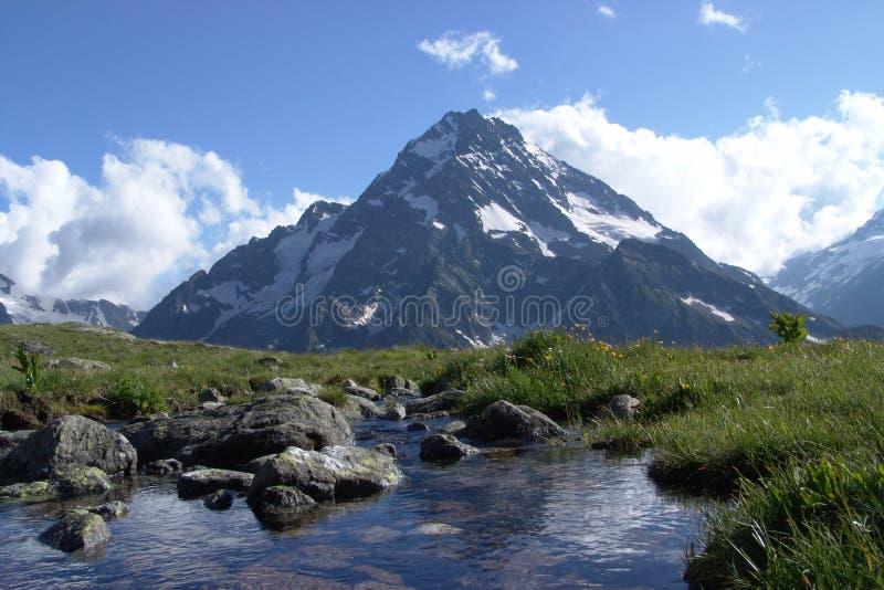 Eine Berglandschaft mit einer Spitze und einem Strom stockfoto