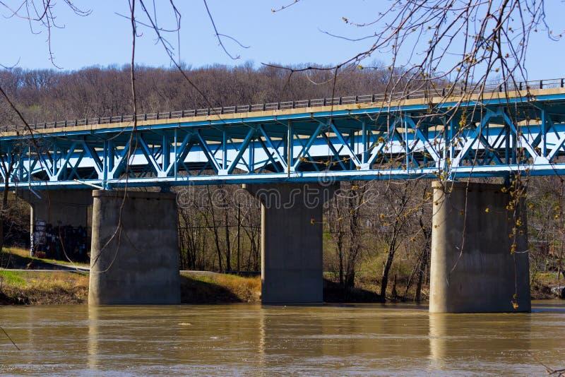 Eine blaue konkrete und Stahlbrücke über einem Brown-Fluss stockbilder