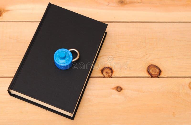 Eine blaue Verriegelung und ein Schwarzbuch stockbild