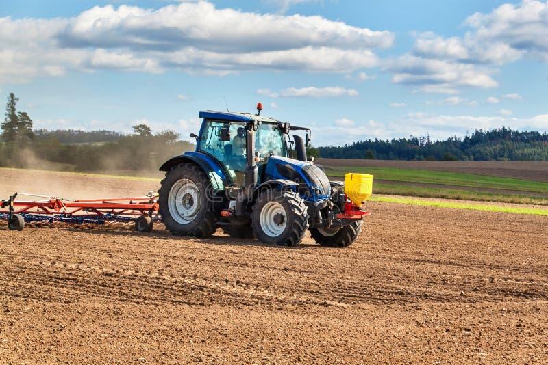 Eine blaue Zugmaschine sät Getreide Landwirtschaftliche Arbeiten auf einem landwirtschaftlichen Betrieb in der Tschechischen Repu lizenzfreie stockfotos