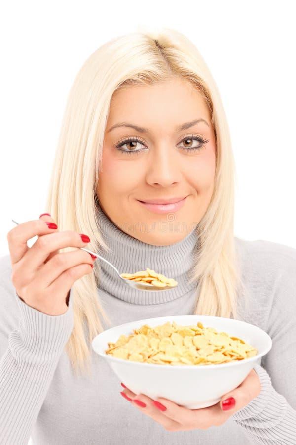Eine blonde Frau, die Corn-Flakes am Frühstück isst stockbild